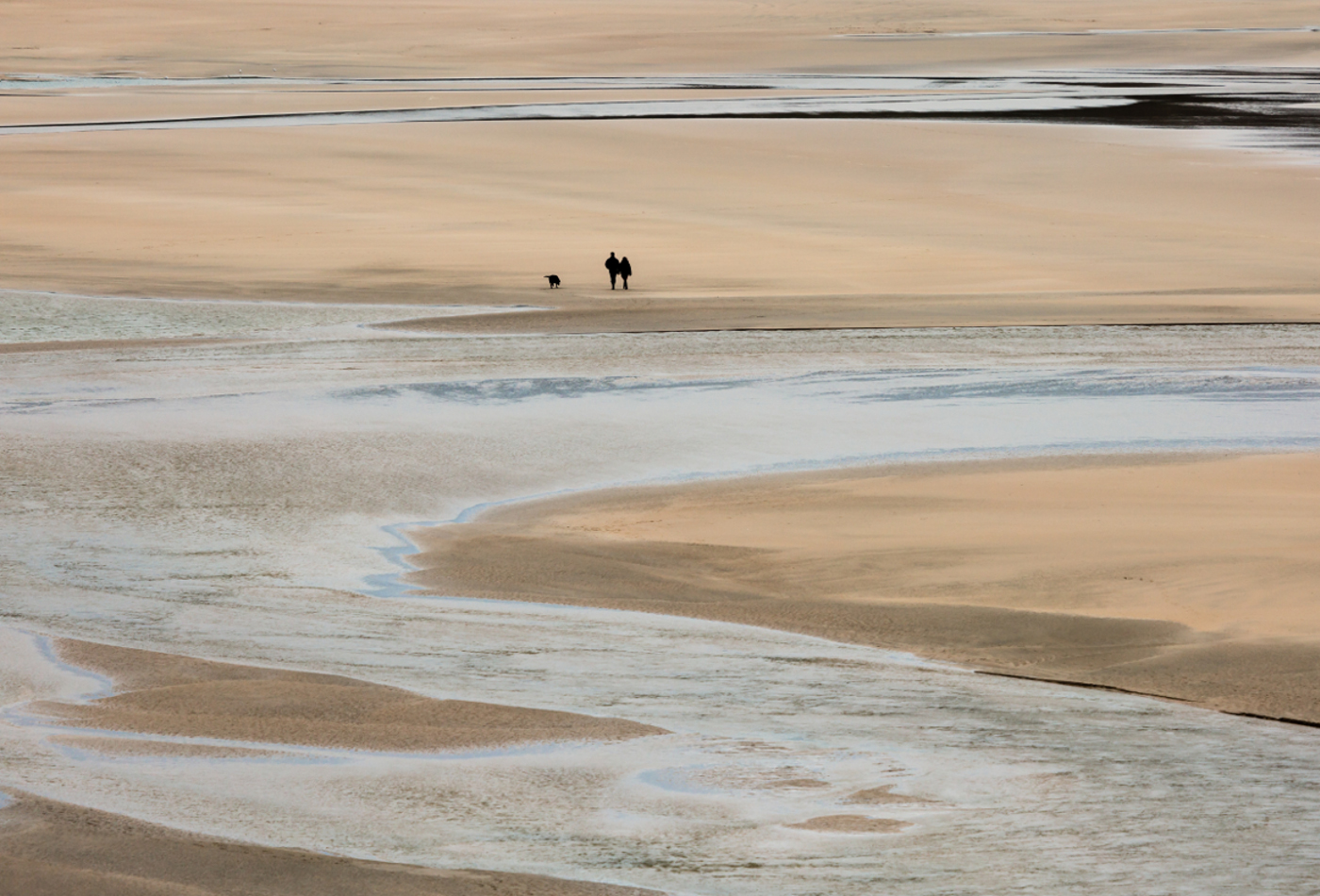 Lone Walkers with dog on Crantock Beach, Cornwall