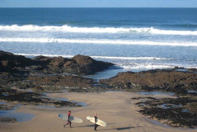 surfers on gwithian towans beach