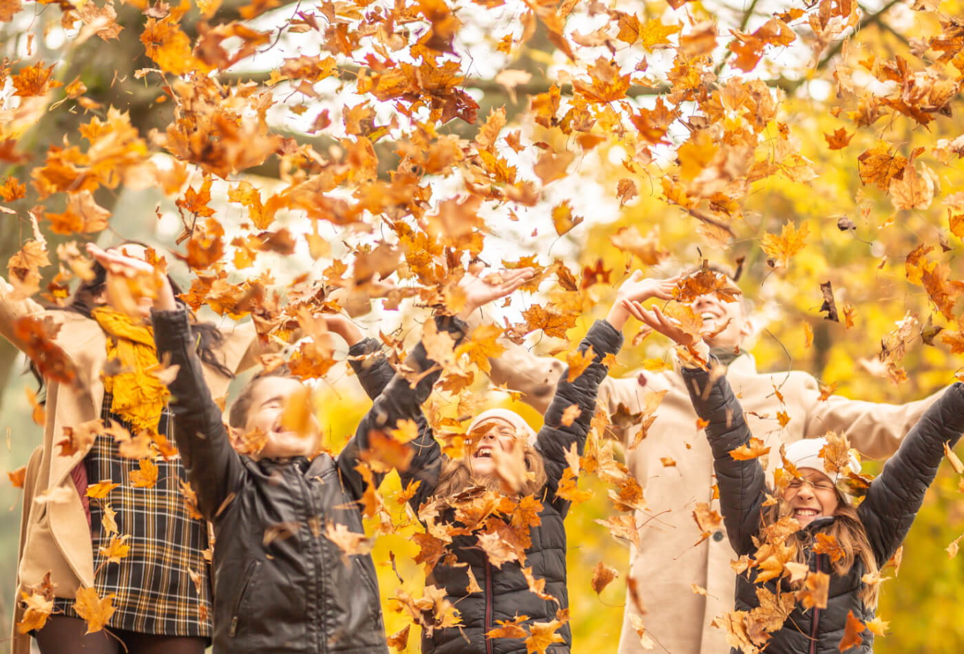 family-throwing-leaves-in-october-half-term-in-cornwall