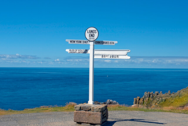 View of Land's End sign in Cornwall, England, with the sea in the background