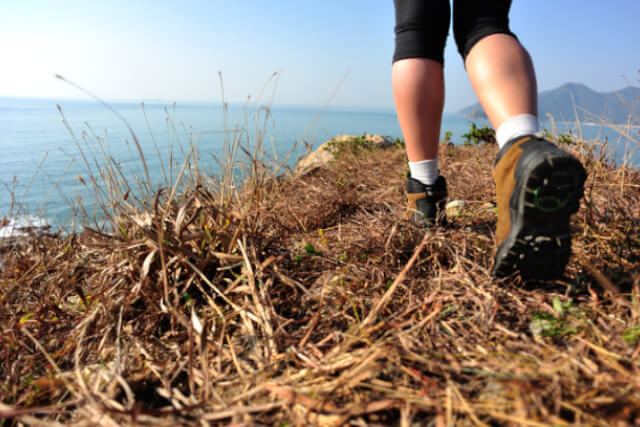 Person wearing walking boots walking along coast with sea in background